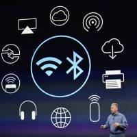 Philip 'Phil' Schiller, senior vice president of worldwide marketing at Apple Inc., speaks during the Apple Inc. Spring Forward event in San Francisco on Monday, in front of a display of the various functions available on the new Apple Watch, which will hit stories in April. | BLOOMBERG