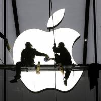 Workers prepare for the opening of an Apple store in Hangzhou, China, in January. Apple will start trading as part of the 30-stock Dow Jones industrial average on March 19. | REUTERS