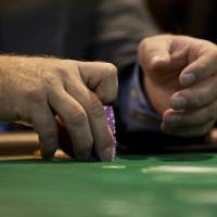 A participant holds a stack of chips at the Global Gaming Expo last May at the Venetian Macao resort and casino, operated by Sands China Ltd. in Macau, China. | BLOOMBERG