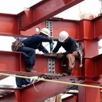 Two people work on a building site in Tokyo in July 2006. Business investment in the October-December quarter rose 2.8 percent from a year earlier. | BLOOMBERG