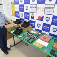A customs officer displays fake products confiscated at Sakaiminato port in Tottori Prefecture last August. | KYODO