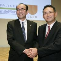 FamilyMart President Isamu Nakayama (right) and Uny Group Holdings Co. President Norio Sako announce the details of their merger talks at a news conference in Tokyo on Tuesday. | KYODO