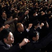 Labor union members raise their hands during an event held by the Japanese Trade Union Confederation in Tokyo on Feb. 5. | BLOOMBERG