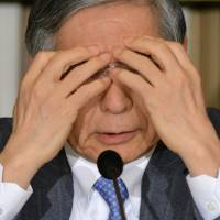 Bank of Japan Gov. Haruhiko Kuroda covers his face as he answers questions during a news conference at the Foreign Correspondents' Club of Japan in Tokyo on Friday. Kuroda spoke to reporters nearly two years after he was sworn in as the central bank chief, with the bank's two-year time-frame for its 2 percent inflation target approaching. | AFP-JIJI