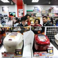 Chinese tourists compare rice cookers at the Laox in Tokyo's Ginza district Feb. 16.   BLOOMBERG