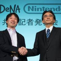 Satoru Iwata (right), president of Nintendo Co., and Isao Moriyasu, president and CEO of DeNA Co., appear at a joint news conference in Tokyo on Tuesday to announce their mobile business tie-up. | BLOOMBERG