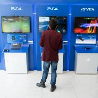 A man plays with a Sony PlayStation 4 in a shop in downtown Shanghai on Thursday. After a two-month delay, the electronics giant launched its PlayStation gaming console in China on Friday, but without some popular titles like 'Grand Theft Auto' and 'Call of Duty.' | AFP-JIJI
