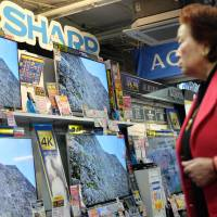 A customer looks at the latest Sharp televisions at an electronics store in Tokyo on Tuesday. The company is considering ceasing all overseas production of LCD televisions except in China. | AFP-JIJI