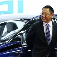 Akio Toyoda, president of Toyota Motor Corp., stands in front of the company's Mirai fuel-cell vehicle during the line-off ceremony of the vehicle at its plant in Toyota, Aichi Prefecture, on Feb. 24. | BLOOMBERG