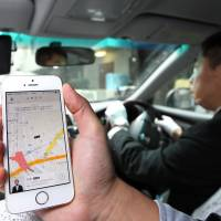 An employee of Uber Japan Co. Ltd. demonstrates its car-sharing service in Tokyo in March last year. The government has told Uber to suspend a pilot project in Fukuoka. | BLOOMBERG