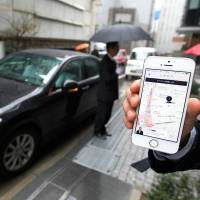 An Uber Japan Co. employee displays the smartphone app he has just used to call the driver (background) and car to the company's Tokyo office in March last year. Uber has suspended its pilot project in the city of Fukuoka after transport authorities objected, citing regulation breaches.   BLOOMBERG