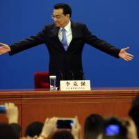 Chinese Premier Li Keqiang invites attendees to sit ahead of a news conference at the end of the National People's Congress in Beijing's Great Hall of the People on Sunday. | AP