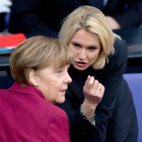 Manuela Schwesig (right), Germany's minister of family affairs, senior citizens, women and youth, speaks with Chancellor Angela Merkel in the lower house of parliament on Thursday in Berlin. | AFP-JIJI