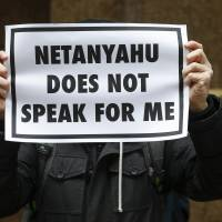 A demonstrator holds a sign during a rally near the Israeli Consulate in New York on Tuesday, after Israeli Prime Minister Benjamin Netanyahu warned U.S. President Barack Obama against accepting a nuclear deal with Iran. | REUTERS