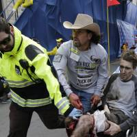 In this photo from April 15, 2013, volunteers and a first responder help victim Jeff Bauman after he was injured in one of two explosions near the finish line of the Boston Marathon. | AP