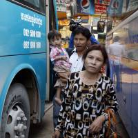 Sam Somaly (front) gets off a bus with her son in-law, Chey Socheat, as he holds her 2-year-old grandson, Be Sokrit, on their arrival at a bus station in Phnom Penh on Feb. 11. | AP