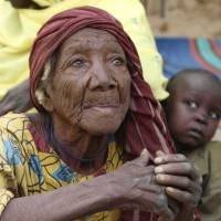 An elderly woman sits on the ground in the recently retaken town of Damasak, Nigeria, on Friday. Soldiers from Niger and Chad who liberated the Nigerian town of Damasak from Boko Haram militants have discovered the bodies of at least 70 people, many with their throats slit, scattered under a bridge. | REUTERS