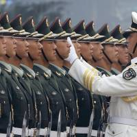 A People's Liberation Army officer uses a string to align soldiers in an honor guard outside the Great Hall of the People in Beijing in September 2013. | REUTERS