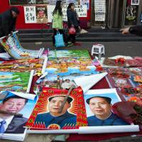 Vendors sell posters of Chinese President Xi Jinping and late leader Mao Zedong on a street of Gujiao in northern China's Shanxi province last month. | AP