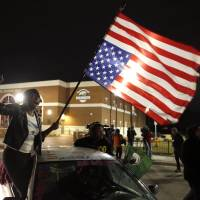 Justice Department clears officer in Ferguson case but criticizes police force