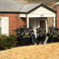 A police tactical team prepares to enter a home in the 100 block of Dade Ave. in Ferguson, Missouri, on Thursday as they search for a suspect they believe to be in the attic as they continue investigating the shooting of two police officers during protests. Two officers were shot in front of the Ferguson Police Department early Thursday while demonstrators were gathered across the street, an attack the county police chief described as 'an ambush' that could easily have killed both men. | AP