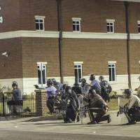 Police officers respond to a fellow officer hit by gunfire outside the Ferguson Police Headquarters in Ferguson, Missouri, Thursday. Two police officers in Ferguson were shot early on Thursday in what officials called an ambush following months of acute tensions over relations between police and minority groups in the St. Louis suburb. | REUTERS