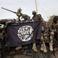 Nigerien soldiers hold up a Boko Haram flag that they had seized in the recently retaken town of Damasak, Nigeria, on Wednesday. Chadian and Nigerien soldiers took the town from Boko Haram militants earlier this week. The Nigerian army said on Tuesday it had repelled Boko Haram from all but three local government districts in the northeast, claiming victory for its offensive against the Islamist insurgents less than two weeks before a presidential election. The insurgents, however, appear to have launched new attacks on Bama and Gamboru, slaughtering women. | REUTERS