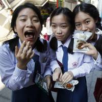 Schoolgirls eat HiSo snacks during a promotional event in Bangkok on Tuesday.   REUTERS