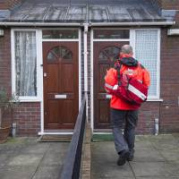 A postman delivers mail to a residential address in London on Friday where Kuwaiti-born London computer programmer Mohammed Emwazi, identified by experts and the media as masked Islamic State militant 'Jihadi John,' is once believed to have lived.   AFP-JIJI