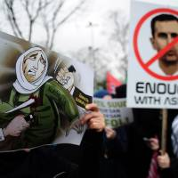 Syrian and Turkish protesters hold up placards and cartoons condemning the Syrian civil war and the regime of President Bashar Assad during a demonstration in Istanbul on Sunday. | AFP-JIJI