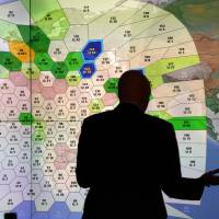 An Inmarsat staff member works in front of a screen detailing various subscribers using their service worldwide at their London headquarters last March. | REUTERS