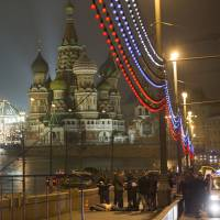 Police gather early Saturday near the body of Boris Nemtsov, a former Russian deputy prime minister and opposition leader who was shot in Moscow's Red Square, near St. Basil's Cathedral (background) and the Kremlin.   AP