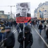 Thousands of Russians marched in Moscow on Sunday in memory of Boris Nemtsov, who was shot dead on Sunday. His murder has sharpened a split in society over the course the country is taking. The sign reads, 'He died for Russia's future'. | REUTERS