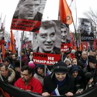 People hold flags and posters during a march to commemorate Kremlin critic Boris Nemtsov, who was shot dead on Friday night, in central Moscow. | REUTERS