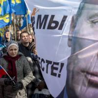 Protesters stand near to a banner with the image of Russian President Vladimir Putin during a rally marking the one-year anniversary of the referendum in Crimea that supported its secession from Ukraine, in Simferopol, Crimea, on Monday. | AP