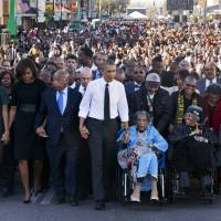 President Barack Obama walks as he holds hands with Amelia Boynton Robinson, who was beaten during 'Bloody Sunday,' as they, the first family and others, including Rep. John Lewis (left of Obama), walk across the Edmund Pettus Bridge in Selma, Alabama, for the 50th anniversary of 'Bloody Sunday,' a landmark event of the civil rights movement, on Saturday. | AP