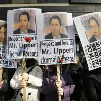Conservative South Korean activists hold portraits of U.S. Ambassador Mark Lippert near the U.S. Embassy in Seoul on Friday during a rally expressing hope for his quick recovery.   AP
