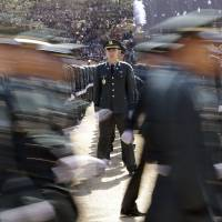 A new South Korean military officer stands still as other officers march during a ceremony in Gyeryong, South Korea, on Thursday. | AP