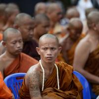 Buddhist monks attend an annual tattoo festival at a temple in Nakhon Chaisi, west of Bangkok, on March 7, 2015. Some Buddhists believe Sak Yant tattoos bring good luck. | AFP