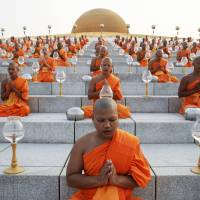 Buddhist monks pray during an alms-offering ceremony at the Wat Phra Dhammakaya temple in Pathum Thani province, north of Bangkok on Makha Bucha Day on March 4. The Dhammakaya temple members include some of Thailand's most powerful politicians and is regarded as the country's richest Buddhist temple. | REUTERS