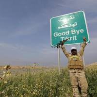 A Shiite fighter gestures in front of a billboard on a street in the town of al-Alam on Monday. Just north of Tikrit, home city of executed Sunni former President Saddam Hussein, Iraqi security forces and Shiite militia fighters began an offensive against Islamic State to regain control over the town of al-Alam.   REUTERS
