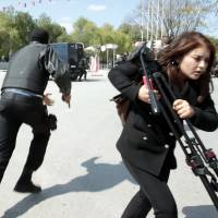 Police officers and a journalist run outside the parliament in Tunis on Wednesday, when gunmen in military uniforms stormed Tunisia's national museum, killing 17 foreign tourists and two Tunisians. | REUTERS