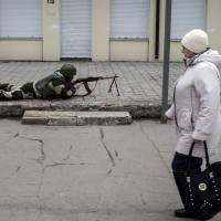 A pro-Russian rebel aims his weapon as a woman passes by during what the rebels said was an anti-terrorist drill in Donetsk, Ukraine, Wednesday. Rebel-held areas of east Ukraine are suffering deteriorating water supplies amid the continued strife. | REUTERS