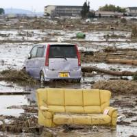 A sofa sits among cars tossed by the tsunami in Wakabayashi Ward, Sendai. | BRETT BULL PHOTOS