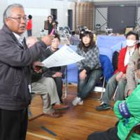 In the Koriyama Junior High School Gymnasium, volunteers receive their assignments.