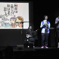 A group of manga artists give an explanation about their project to auction original prints of their cartoons during the 'PechaKucha — Inspire Japan' event Saturday night. | YOSHIAKI MIURA PHOTOS