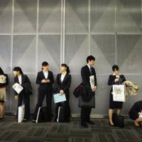 All educated and nowhere to go: Graduates wait in line before attending a company's briefing session as they look for a job in Tokyo on Jan. 22. | AP PHOTO