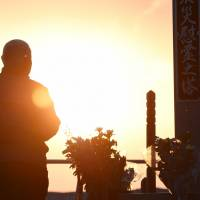 A man prays for victims of the March 11, 2011, quake-tsunami disaster at a memorial site in the city of Sendai on Wednesday. | KYODO