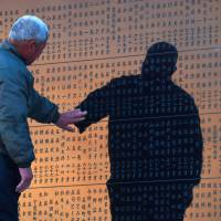 Namio Matsuki, 79, touches the name of a fisherman friend who died in the March 2011 disasters at a cenotaph early Wednesday in Sendai. | KYODO