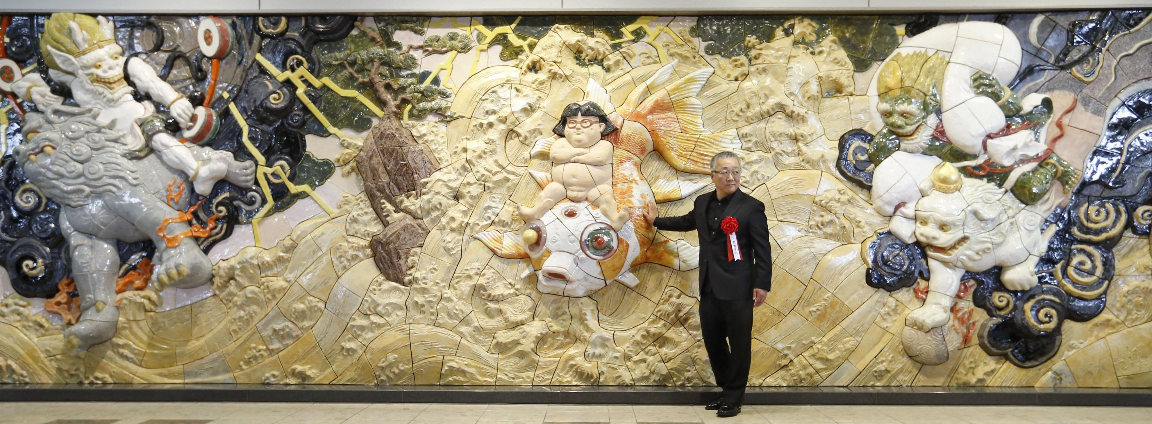 Internationally renowned manga artist Katsuhiro Otomo stands next to a porcelain relief unveiled Thursday at Sendai Airport for victims of the 3/11 disasters. | KYODO